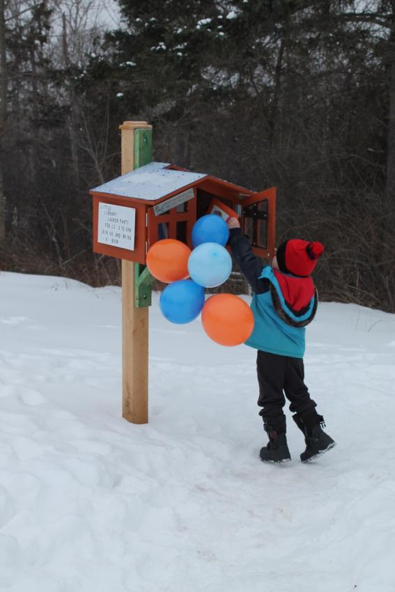 Sam puts a book in the Little Free Library